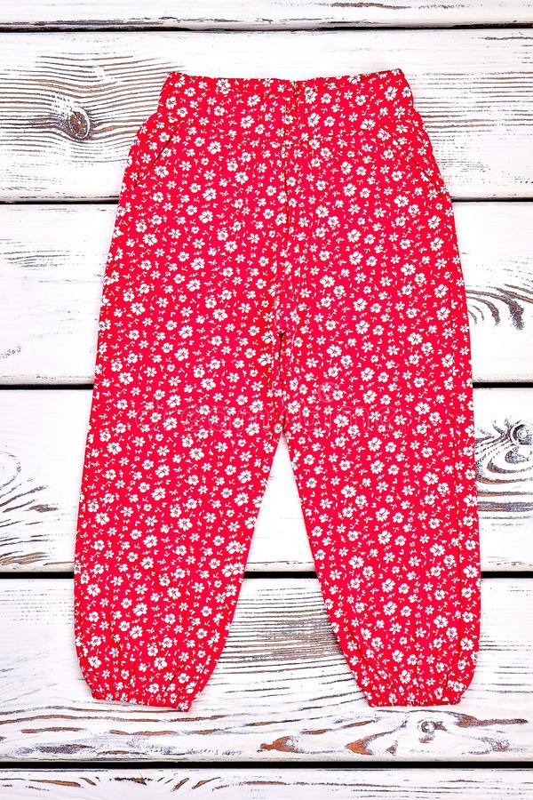 Infant girl red patterned trousers. Little girl red summer trousers in floral print, old wooden background. Kids summer apparel on sale. Baby harem pants stock photography