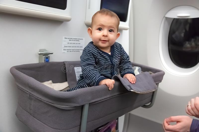 Infant girl sit in special baby bassinet in airplane. She is laugh and amazed, it is her first flight.  royalty free stock images