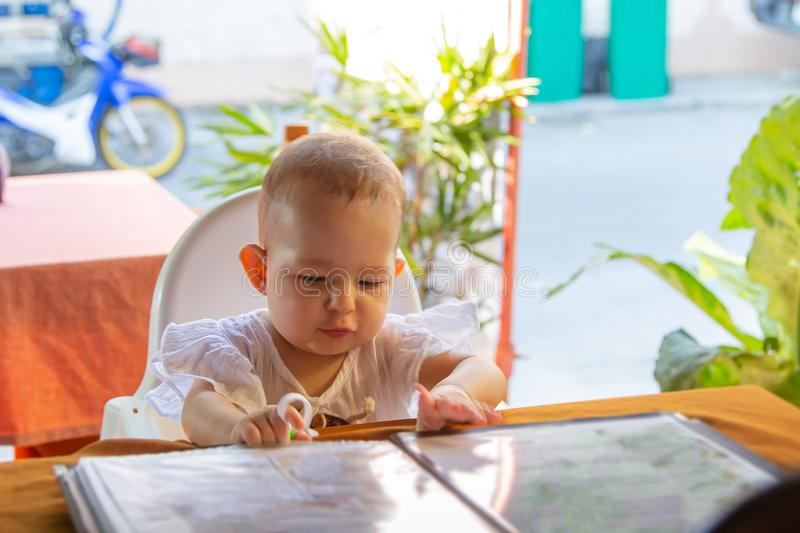 Infant girl is sitting on a baby`s high chair in a street cafe. Children reading chooses and studies the menu in the restaurant royalty free stock photography