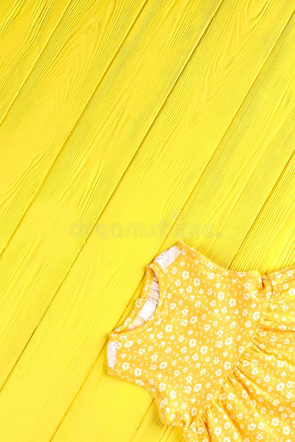 Infant girl vintage print dress. Baby-girl yellow sleeveless printed dress on colored wooden background, top view. Kids summer apparel royalty free stock photo