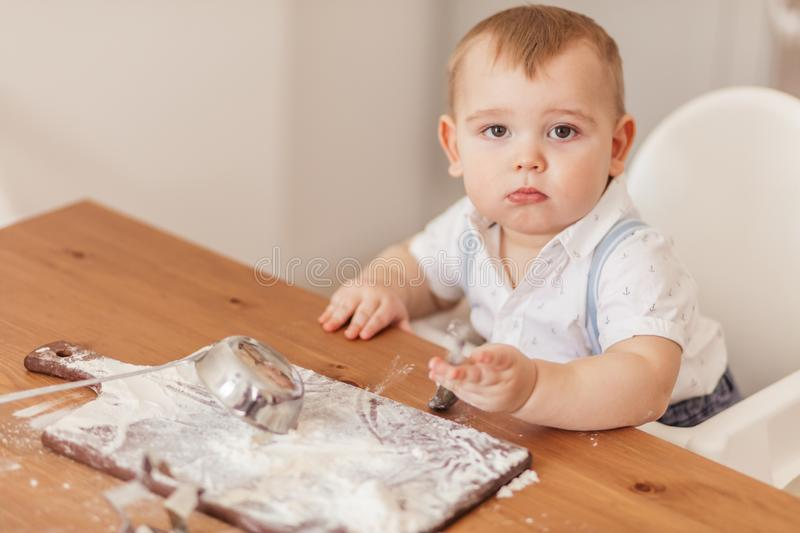 Infant little cooker boy helps to make cakes sitting at table with flour spread. royalty free stock photo
