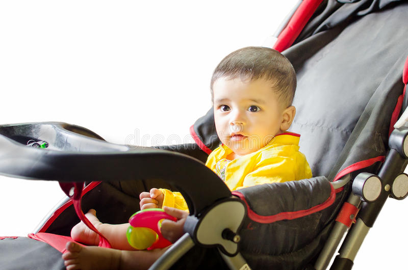 Infant playing on black & red stroller. Wearing yellow shirt isolated in white background royalty free stock photo
