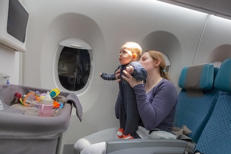 Infant plays on mother hands at the airplane. Amazed of tablet monitor and flight. Plane baby bassinet on the foreground royalty free stock photography