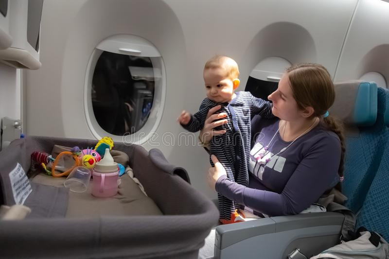 Infant plays on mother hands at the airplane.  Interest to special baby bassinet during the flight.  stock photography