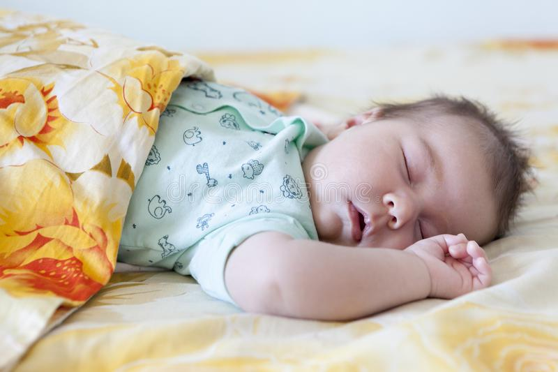 Infant sleep covered with blanket, large bed, closed eyes and hand up. Infant sleep covered with a blanket, large bed, closed eyes and hand up royalty free stock images