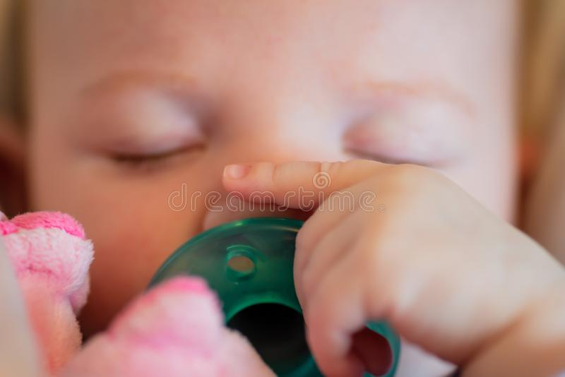 Closeup of baby with pacifier sleeping in car seat - soft focus royalty free stock images