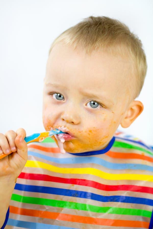 Infante che mangia con l'alimento intorno al suo fronte immagine stock