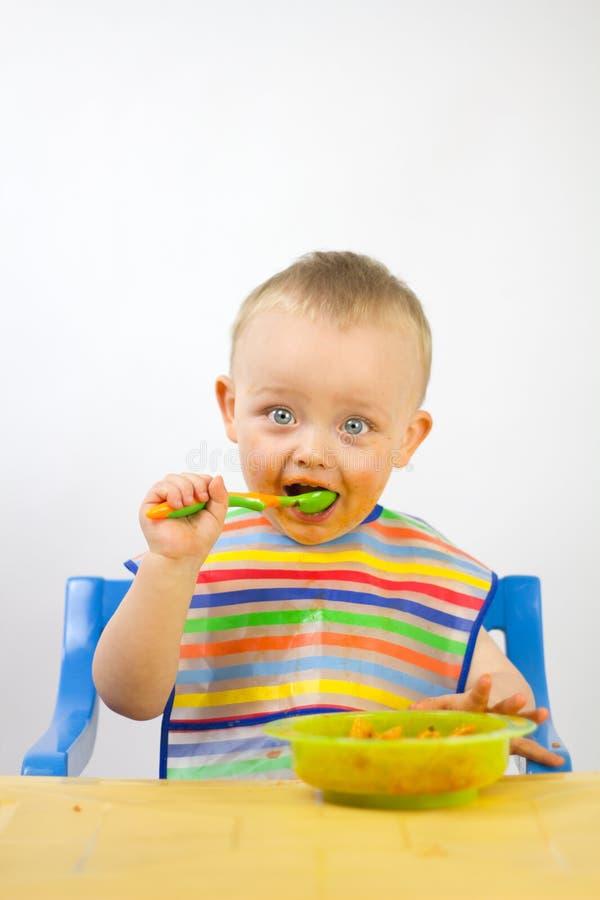 Infante che mangia i suoi primi pasti fotografie stock