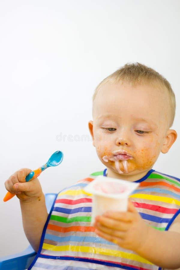 Infante che mangia sudicio yogurt fotografie stock
