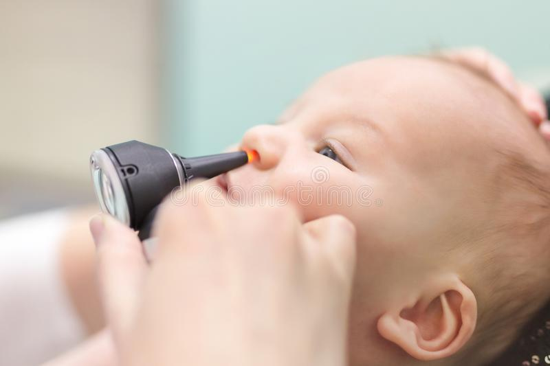 Infante in clinica pediatrica Mano del ` s di medico del primo piano con il naso d'esame del ` s del bambino dell'otoscopio moder fotografie stock