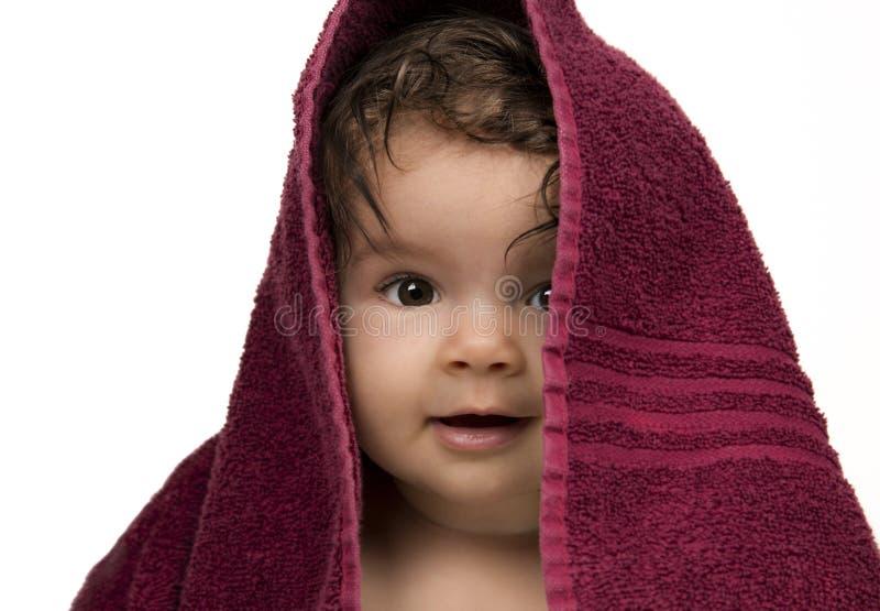 Infante que olha para fora de debaixo da toalha vermelha fotografia de stock royalty free