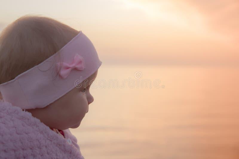 Infante que procura a primeira vez no mar - por do sol paisagem alaranjada bonita imagem de stock