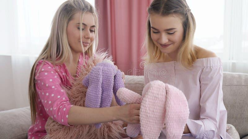 Infantile lifestyle teen girl toy leisure childish. Infantile lifestyle. teenage girls holding toy bunnies. youth leisure communication. childish behavior royalty free stock image