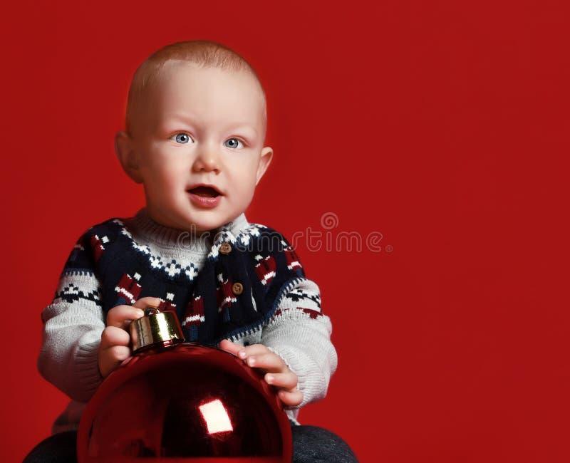 Infanzia e concetto della gente - piccolo neonato felice con la palla a casa sopra neve fotografia stock libera da diritti