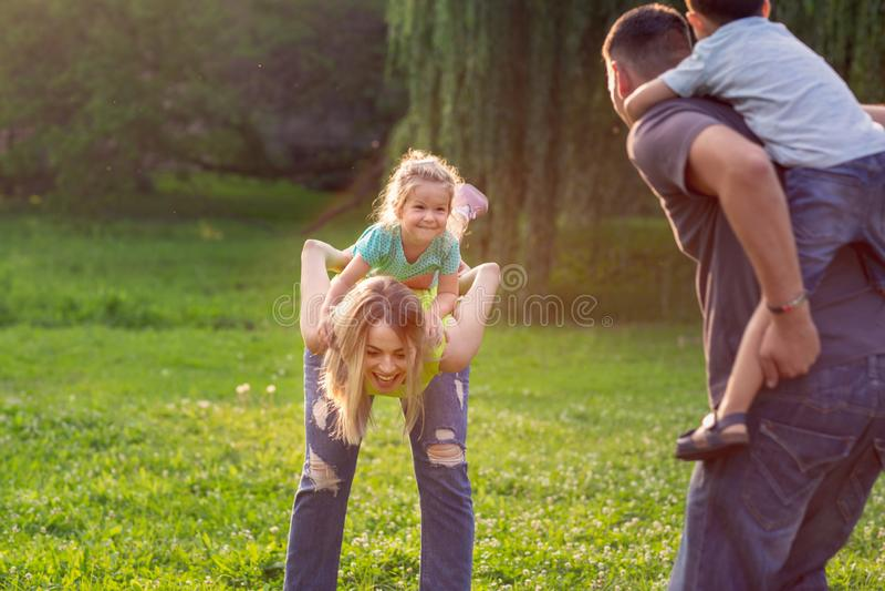 Infanzia felice - la famiglia trasporta sulle spalle i loro bambini e si diverte insieme in parco fotografie stock