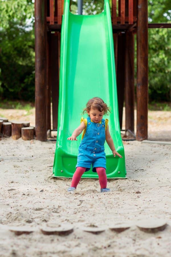 Infanzia felice - ragazza che fa scendere giù lo scorrevole al campo da giuoco fotografie stock