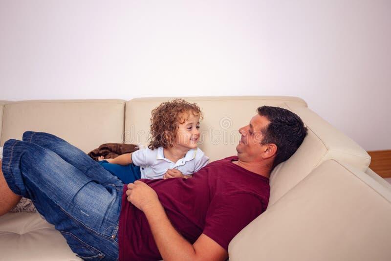 Infanzia felice - ragazzo sveglio che gioca con il padre a casa immagine stock libera da diritti