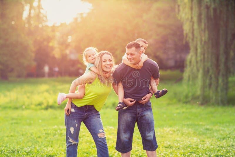Infanzia-genitori felici che giocano con i loro bambini nel parco fotografie stock libere da diritti