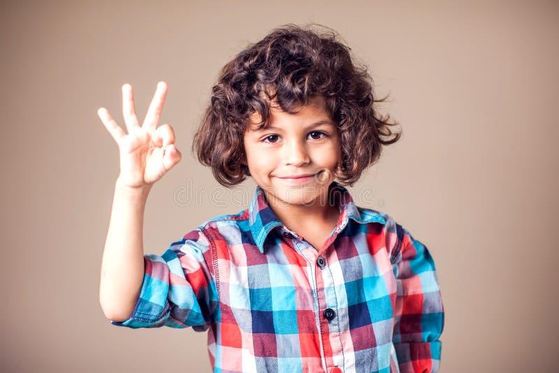 Infanzia, moda, pubblicità e ideologia delle persone - un ragazzo felice che mostra il segno della mano fotografia stock