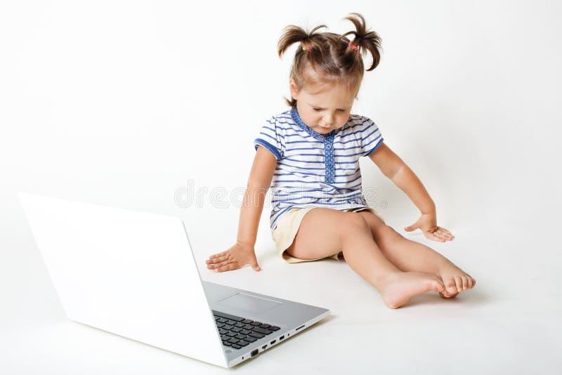 Infanzia nell'era digitale Il bambino attraente starnutisce e fa chiudere gli occhi, guarda giù, si siede vicino al computer port fotografia stock libera da diritti