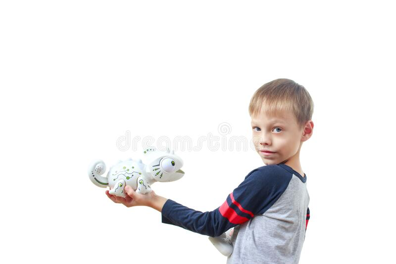 Infatuated child boy playing plastic toy lizard robot with a remote control, isolated on white background. The nano-toy Chameleon. Spat out a tongue in the royalty free stock photography