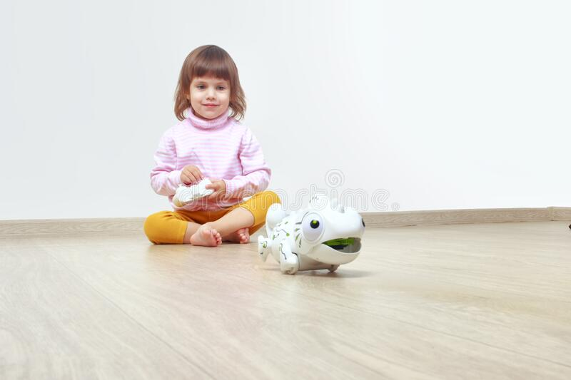 Infatuated cute little girl playing plastic toy lizard robot with a remote control. The nano-toy chameleon, modern technology of. Toys. Electronic pet royalty free stock photo