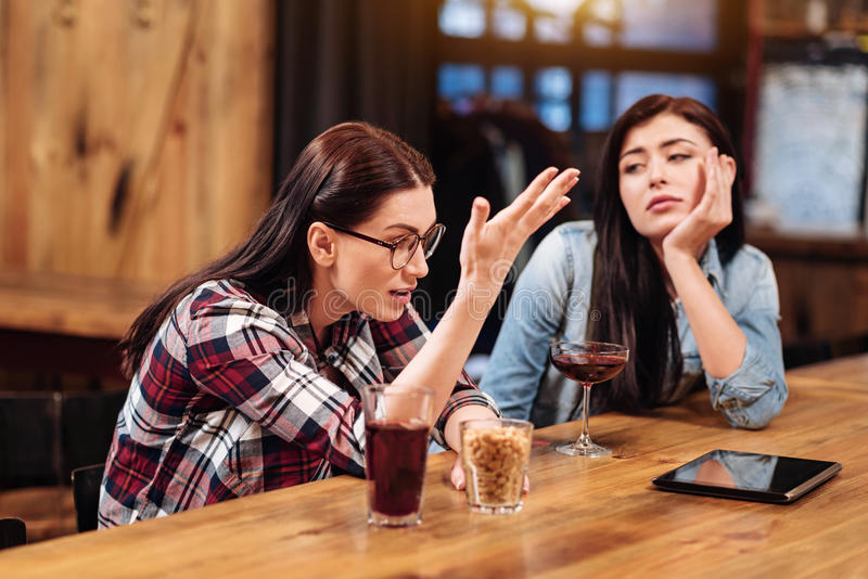 Infatuated with discussion girl holding glass with peanuts. It was hard day. Disturbed female wearing checked shirt speaking with her best friend while actively stock image
