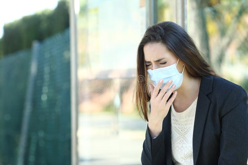 Infected woman wearing a mask coughing in a bus stop stock photo