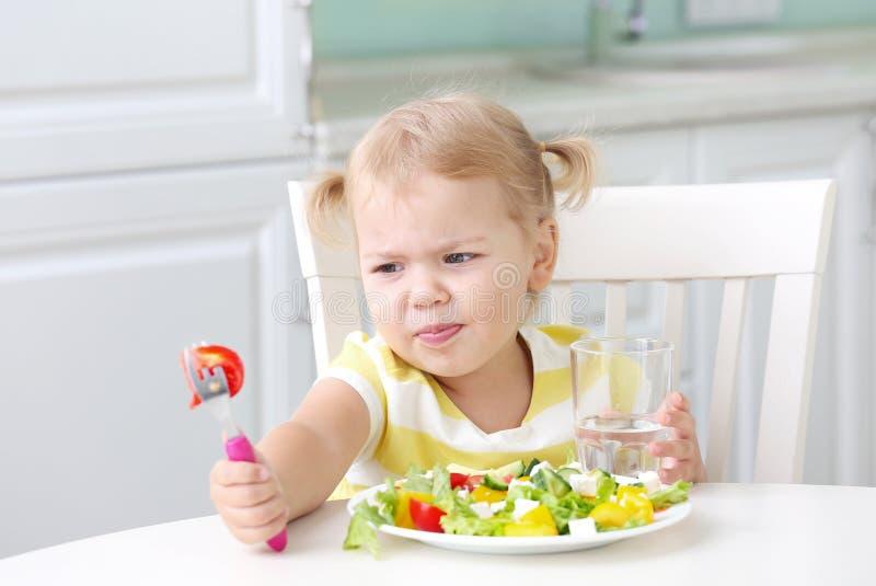 Infeliz e descontente ao comer comida saudável fotografia de stock royalty free