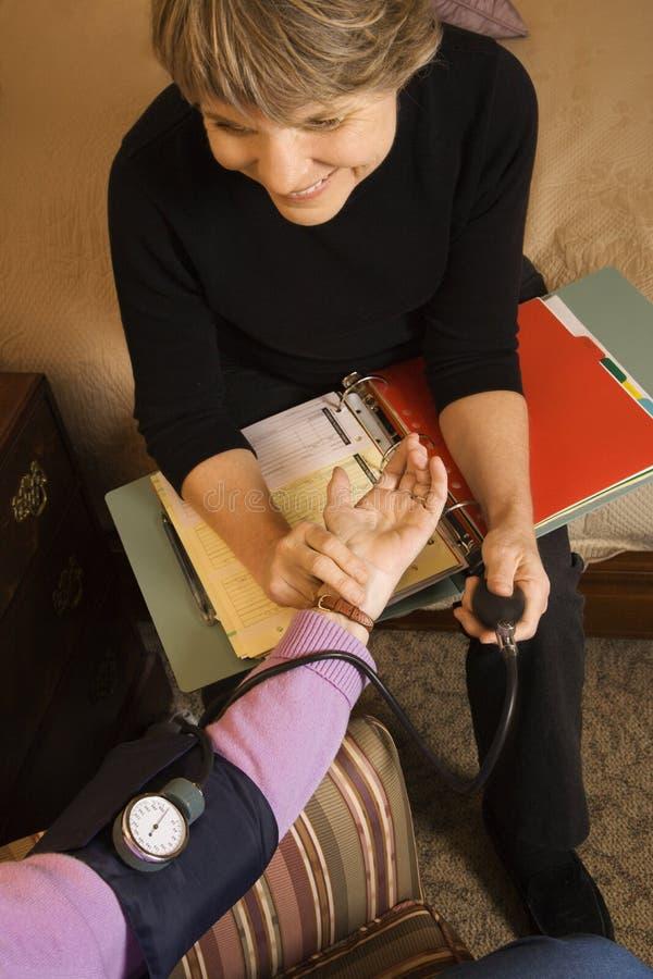 Infermiera che cattura pressione sanguigna della donna anziana. fotografia stock libera da diritti
