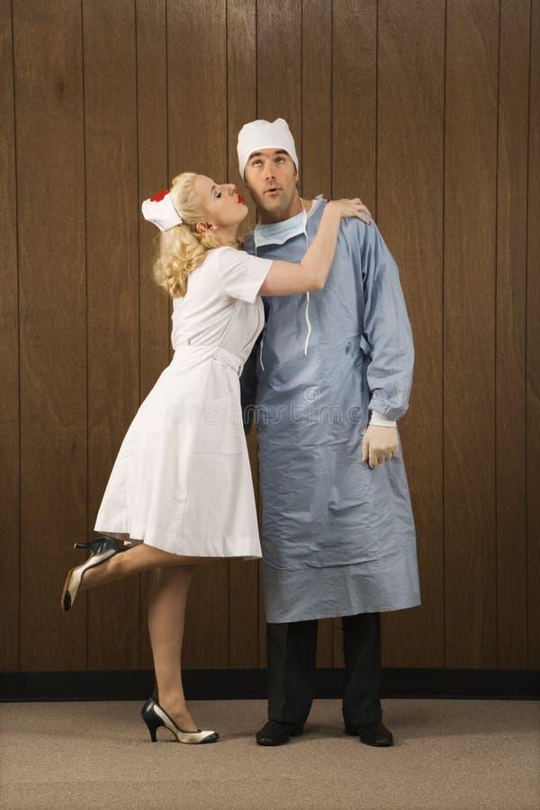 Infermiera femminile che bacia chirurgo sulla guancica. immagini stock
