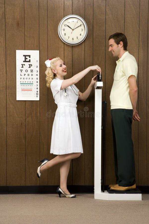 Infermiera femminile che pesa uomo sulla scala. fotografia stock libera da diritti