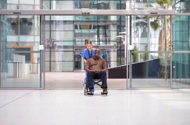 Infermiera Femminile Indossa Crubini Ruotando Il Paziente In Sedia A Rotelle Attraverso La Lobby Dell'Edificio Ospedale Moderno immagini stock libere da diritti
