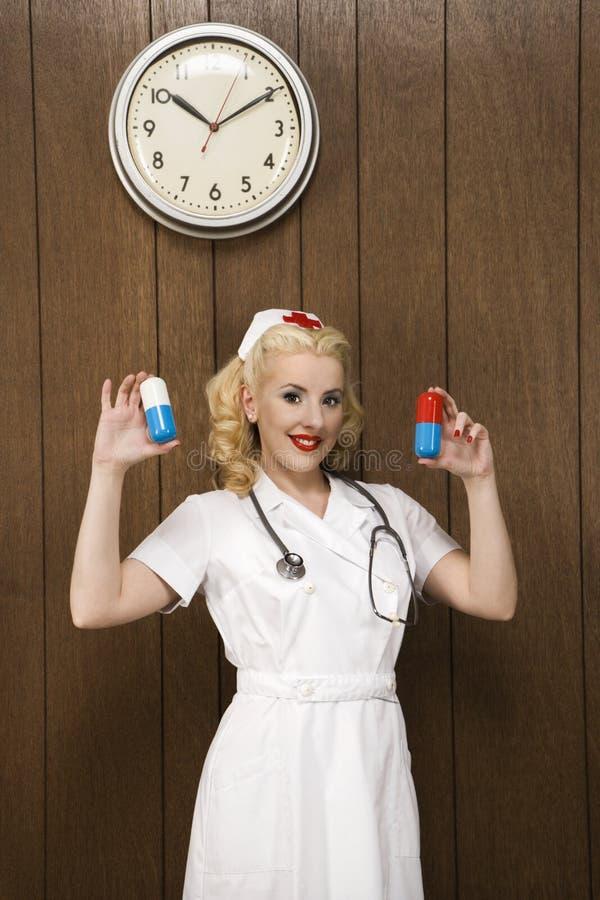 Infermiera femminile nelle retro pillole uniformi del gigante della holding. fotografia stock libera da diritti