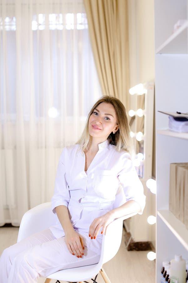 Infermiere affascinante che si siede nella sedia al gabinetto ed al vestito bianco d'uso immagini stock