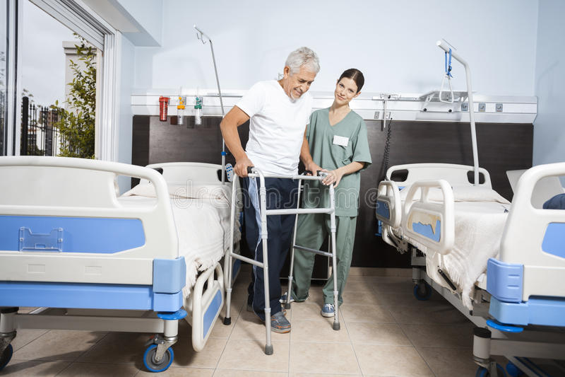 Infermiere Assisting Senior Patient nel usando Walker At Rehab Center fotografia stock