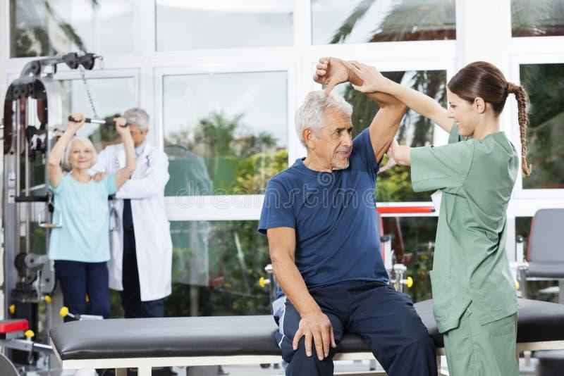 Infermiere Assisting Senior Woman nell'esercizio di braccio nel centro di riabilitazione fotografie stock