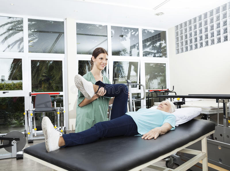 Infermiere Assisting Senior Woman nell'esercizio di gamba al centro di riabilitazione immagini stock libere da diritti