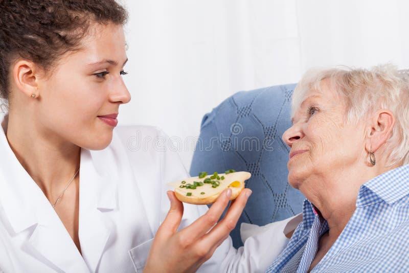 Infermiere che alimenta donna anziana fotografia stock