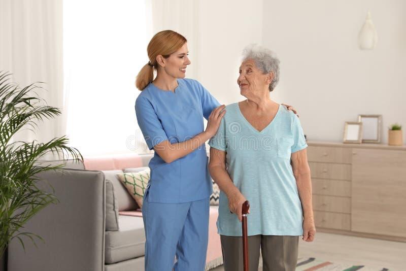 Infermiere che assiste donna anziana con la canna immagine stock libera da diritti