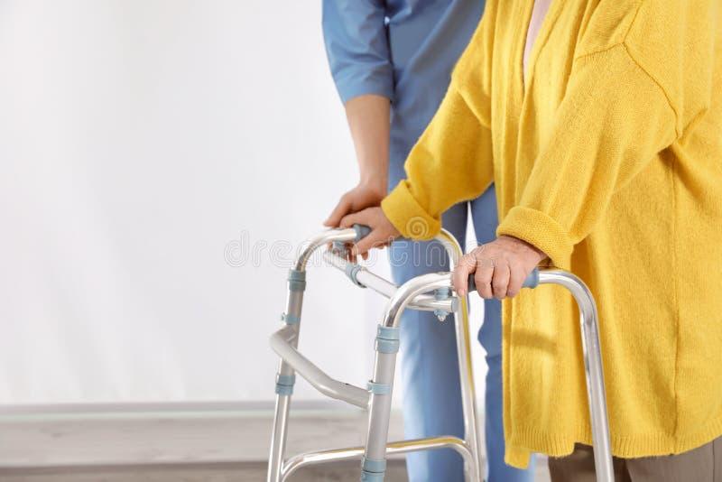 Infermiere che assiste donna senior con il camminatore in ospedale, primo piano fotografie stock libere da diritti