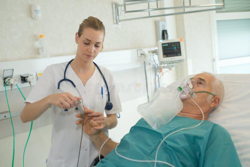 Infermiere che attacca il monitor di impulso al paziente anziano fotografie stock