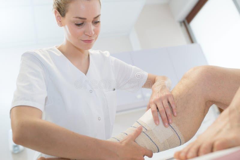 Infermiere che benda la gamba dei pazienti immagine stock