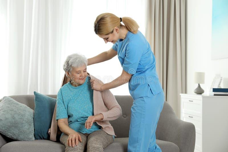 Infermiere che copre donna anziana di coperta Assistenza della gente senior fotografie stock libere da diritti