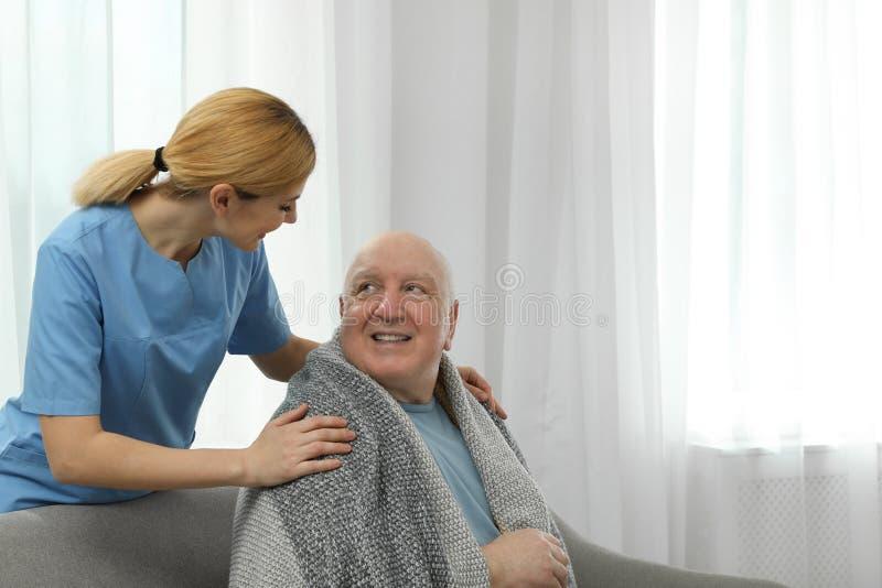 Infermiere che copre uomo anziano di coperta all'interno Assistenza della gente senior fotografia stock