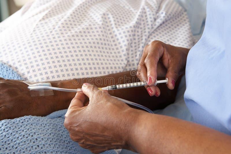 Infermiere che inietta paziente maschio senior nel letto di ospedale fotografie stock