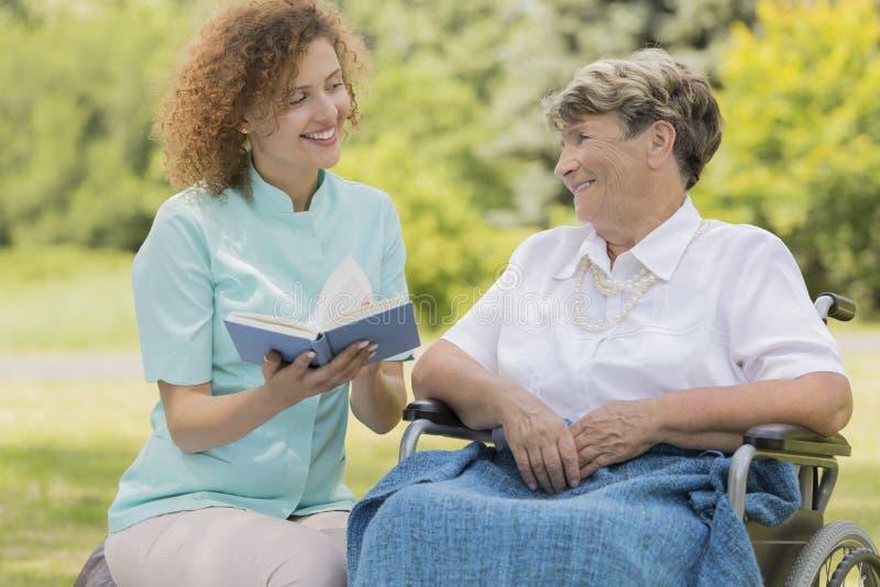 Infermiere che legge donna anziana in un giardino immagine stock