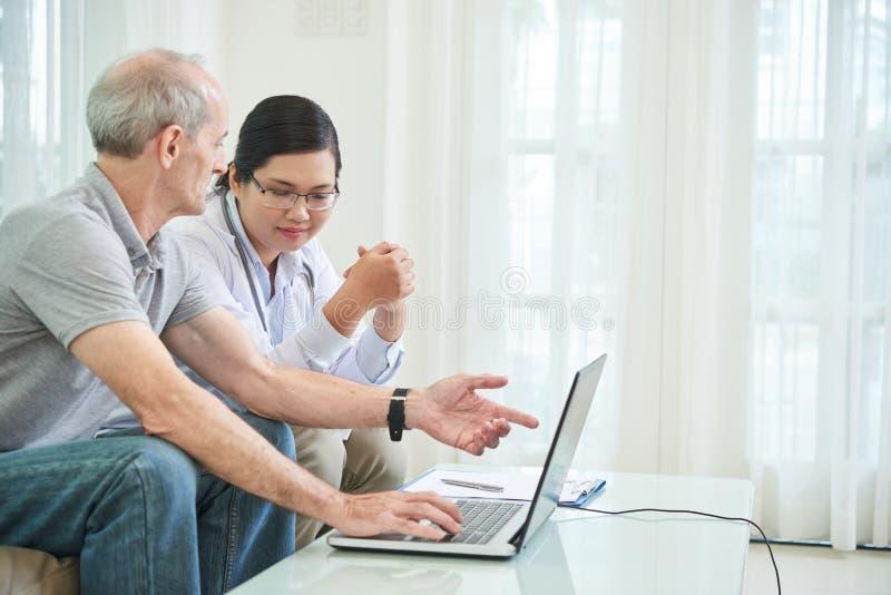 Infermiere che parla con paziente a casa immagine stock