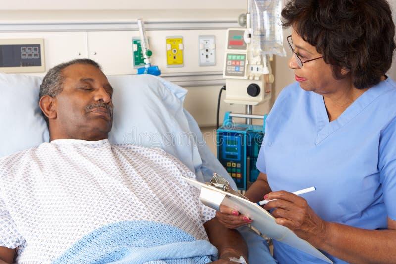 Infermiere che parla con paziente maschio senior sul reparto fotografia stock