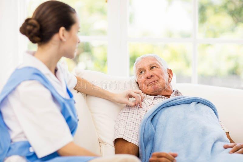 Infermiere che prende cura del paziente anziano malato immagine stock